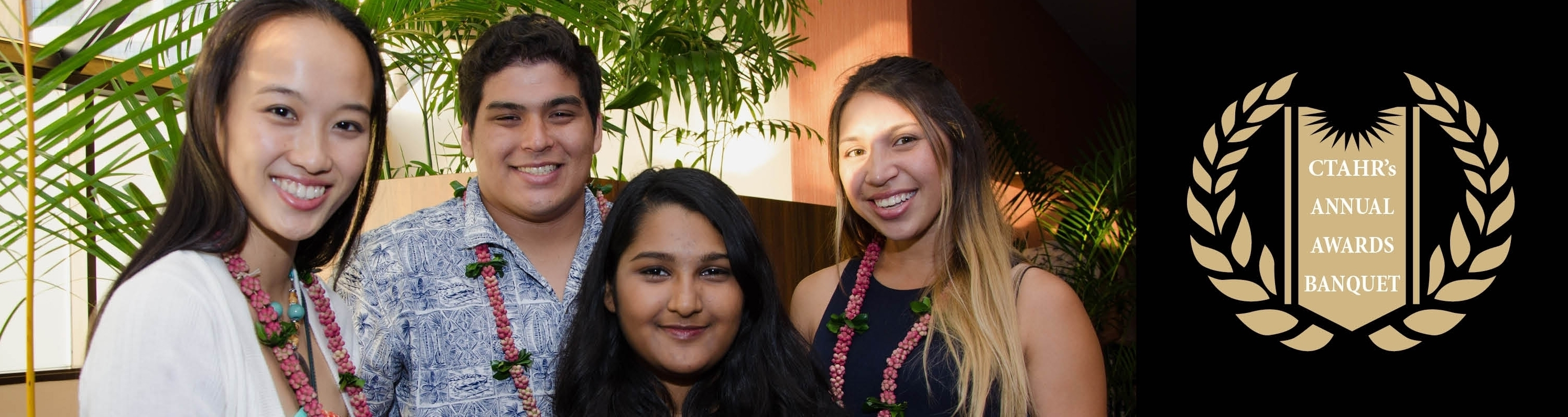 four smiling student next to CTAHR Banquet mark