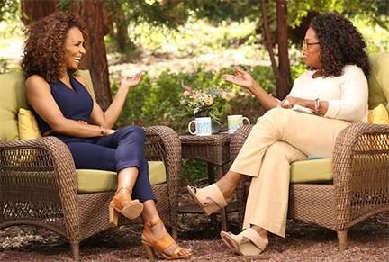 Janet Mock seated talking to Oprah Winfrey