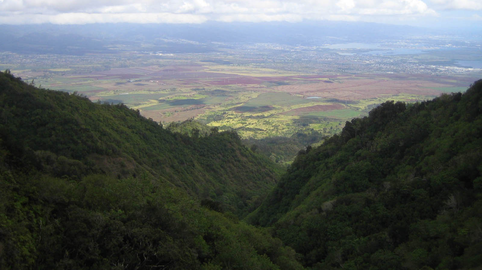 View through a green mountain valley with farm fields in the distance.